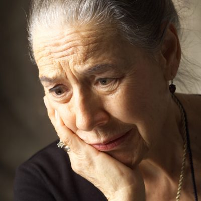 an elderly woman with a gray haired bun is wearing a dark dress and in leaning on her hand looking worried
